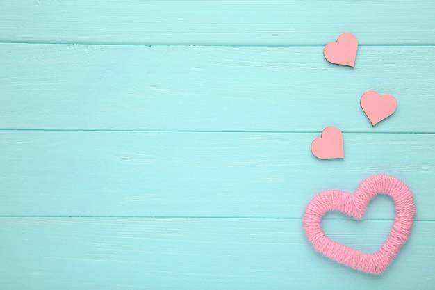青色の背景に赤い糸の心。ピンクの心