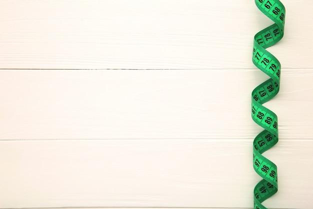 白い背景の上の仕立て屋の測定テープ