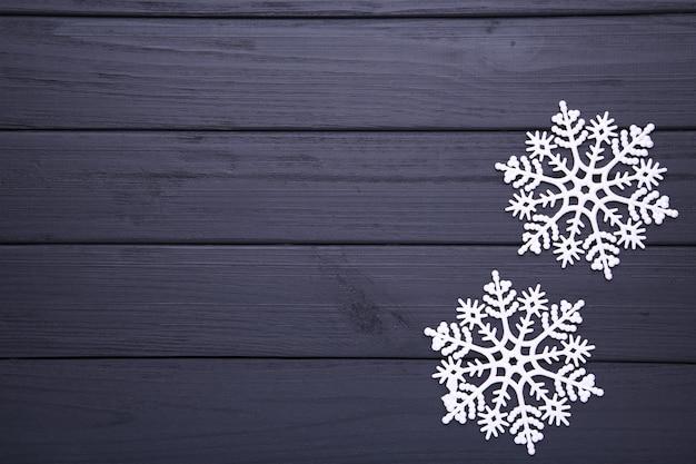 黒い木製の背景に雪の結晶。クリスマスのコンセプト。