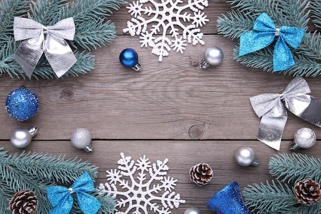 クリスマスの飾り。ボール、バンプ、スノーフレーク、灰色の背景に弓とモミの木の枝
