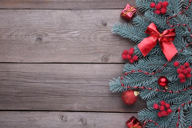 クリスマスの飾り。ボール、バンプ、ガマズミ属の木の果実、灰色の背景にギフトとモミの木の枝