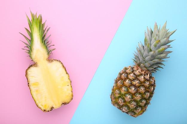 パイナップルとカラフルな背景にパイナップルの半分