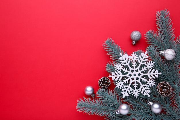 クリスマスの飾り。ボール、バンプ、赤の背景にスノーフレークとモミの木の枝