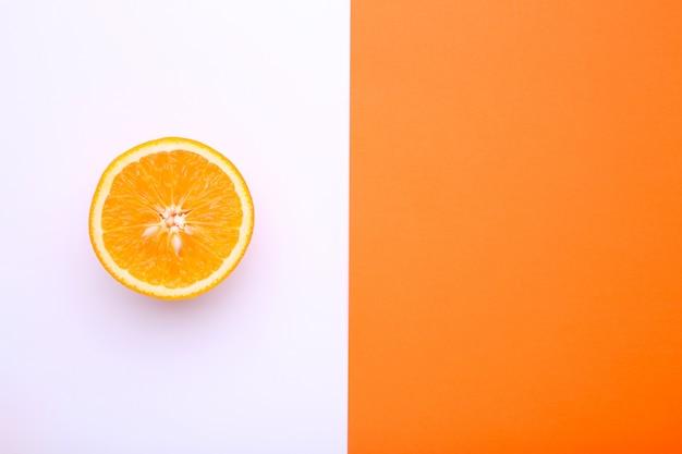 カラフルな背景に熟したオレンジ色の果物