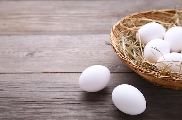 灰色の木製の背景上のバスケットの鶏の卵