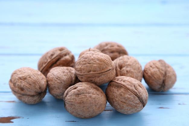 青い木製の背景にクルミカーネル。クルミの健康食品