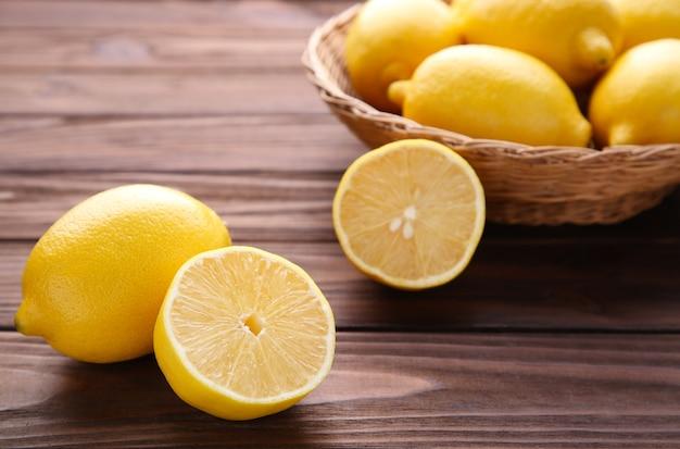 茶色の木製の背景にバスケットで新鮮なレモン。トロピカルフルーツ。