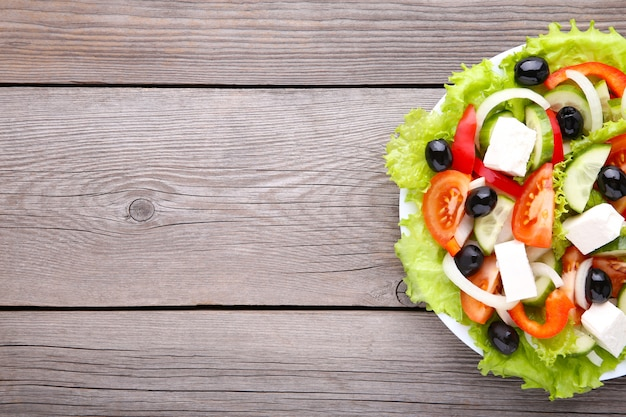Свежий греческий салат на серой деревянной