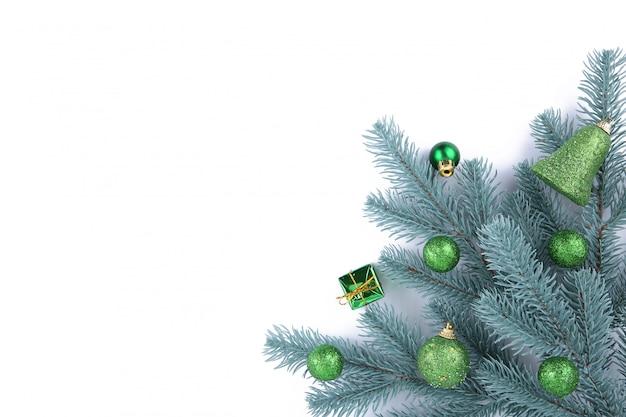 白い背景の上のクリスマスの装飾とクリスマスツリーの枝