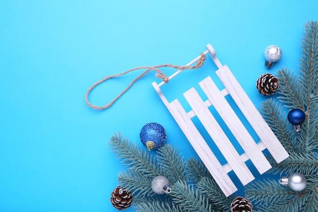 青色の背景にモミの木の枝でクリスマスグッズそり
