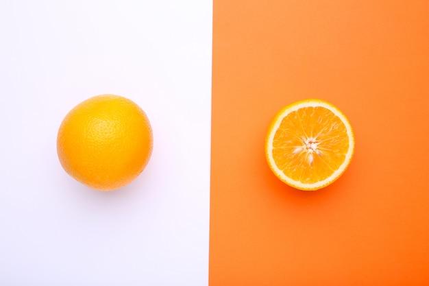 Спелый апельсин на цветном фоне