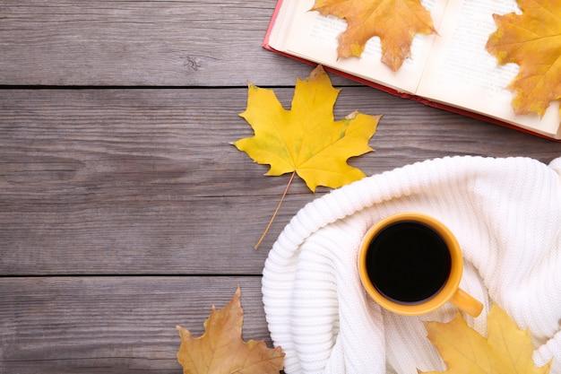 秋の紅葉と木製の背景上の古い本とコーヒーのカップ