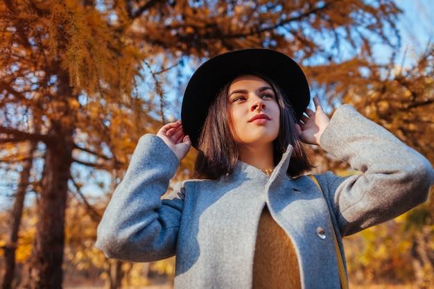 秋のファッション。若い女性のスタイリッシュな服を着て、屋外の帽子を保持しています。衣類とアクセサリー