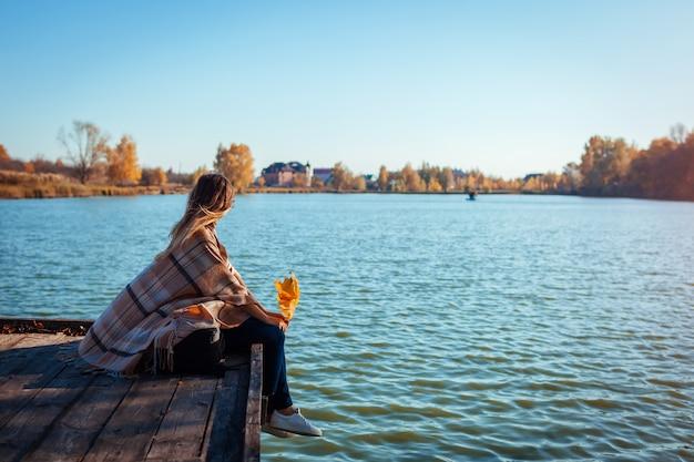 Путешественник с рюкзаком, расслабляющий осенью река на закате. молодая женщина, сидя на пирсе, любуясь пейзажем