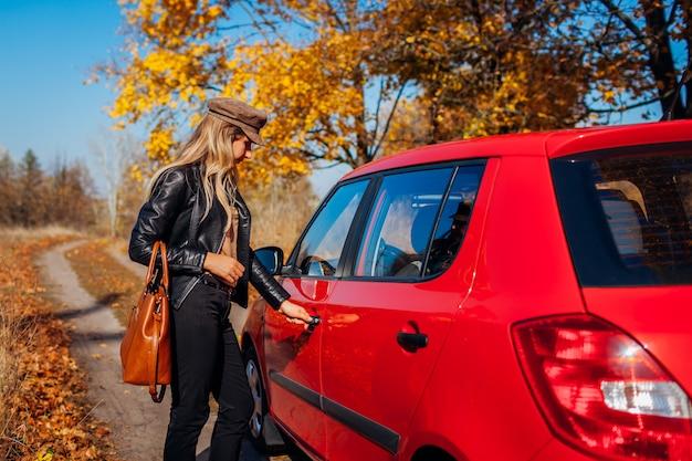 Открытие двери автомобиля. женщина открывает красную машину с ключом на осенней дороге