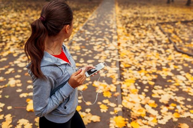 女性は、秋の公園で走る前に音楽をつけています。健康的な生活様式
