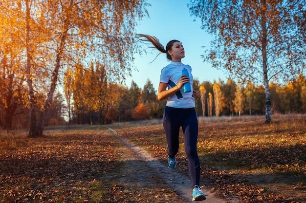 秋の公園でランナートレーニング。水のボトルを実行していると日没で健康を保つ女性。アクティブなライフスタイル