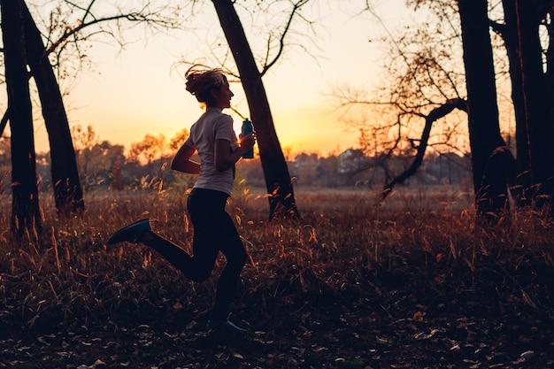 秋の公園でランナートレーニング。日没時の水のボトルで走っている女性。アクティブなライフスタイル。シルエット