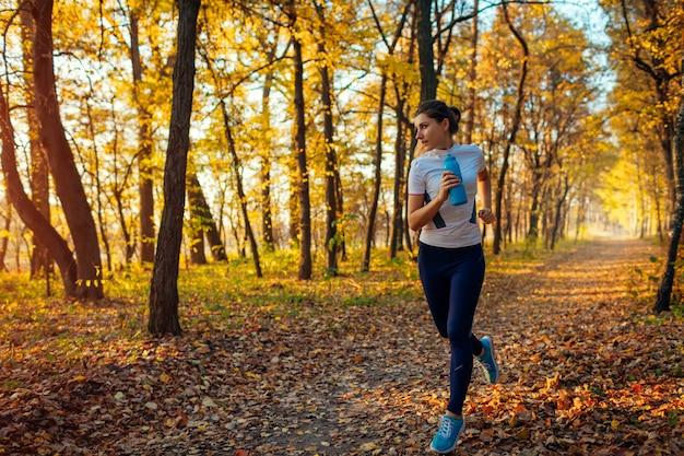 秋の公園で運動するランナー。日没時の水のボトルで走っている女性。アクティブで健康的なライフスタイル