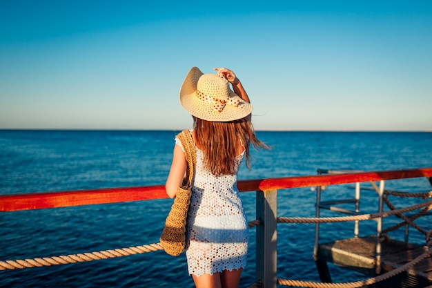 観光。紅海の桟橋の景色を眺める若い女性旅行者。夏のファッション