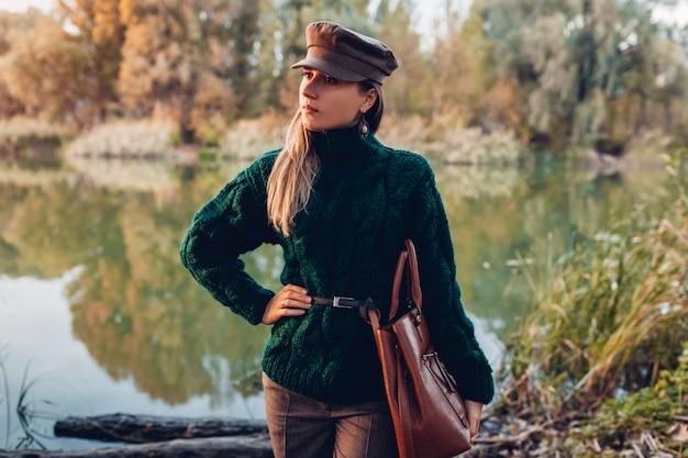 秋のファッション。スタイリッシュな服を着て、屋外のハンドバッグを保持している若い女性。衣類とアクセサリー