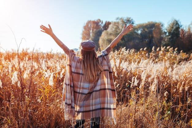 秋のファッション。屋外のスタイリッシュなポンチョを着ている若い女性。服とアクセサリー。手を上げる幸せな女の子