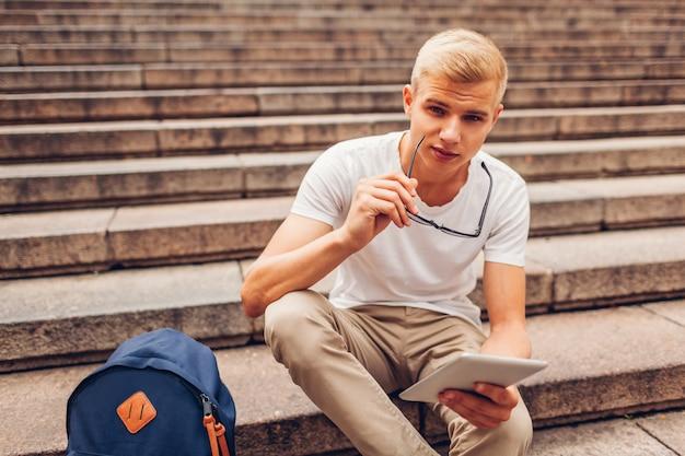 タブレットを使用して階段の上に座っているとメガネを保持しているバックパックを持つ大学生。屋外で勉強する人