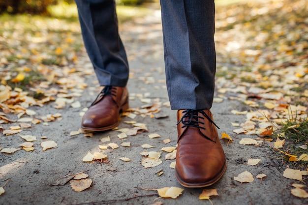 秋の公園で靴を着ているビジネスマン。茶色の革の古典的な靴。足のクローズアップ