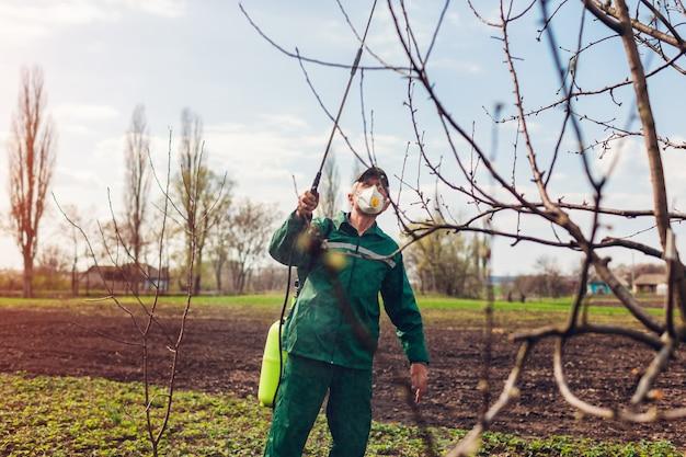 秋の庭の昆虫に対して手動農薬噴霧器で木を噴霧する農家。農業および園芸