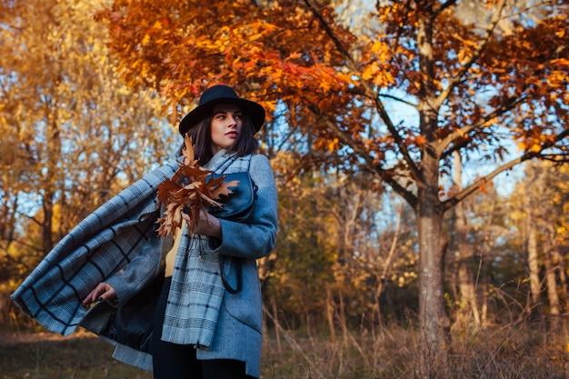 秋のファッション。スタイリッシュな服を着て、財布を持って公園を歩いている若い女性。衣類とアクセサリー