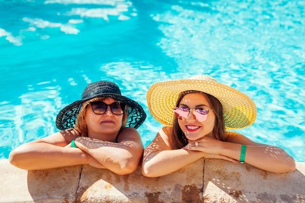年配の女性がホテルのスイミングプールで彼女の大人の娘と一緒にリラックス。休暇を楽しんでいる人。母の日
