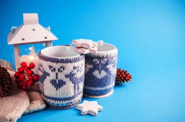 青色の背景にニットのクリスマスケースに身を包んだホットドリンクのカップ。