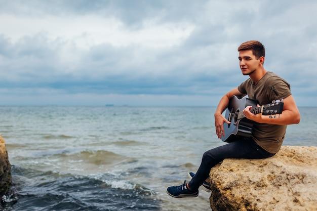 雨の日に岩に囲まれたビーチでアコースティックギターを弾く若い男