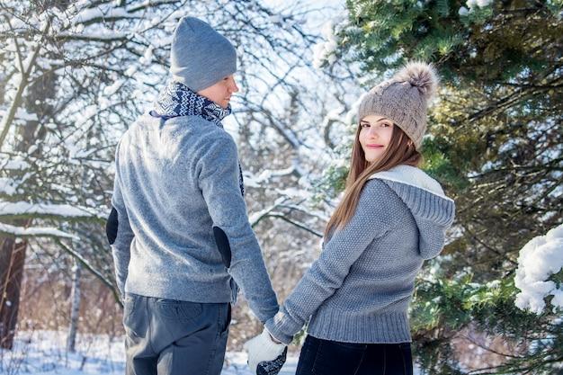 愛の若いカップルが森の中を歩く