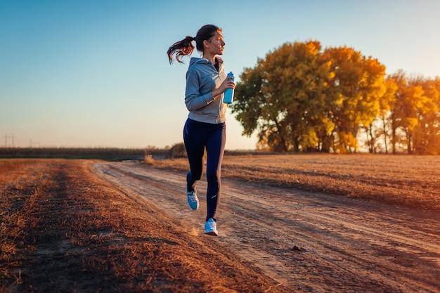 夕暮れ時の秋のフィールドで走っている女性。健康的なライフスタイルのコンセプトです。アクティブなスポーツの人々