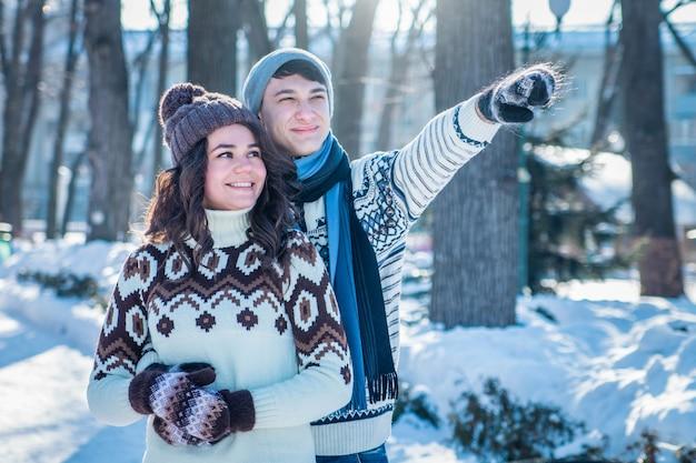 Влюбленная пара обнимается в зимнем парке