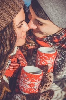 カップルは冬の公園で熱いお茶を飲む