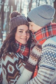 愛のカップルは冬の公園で抱擁します。