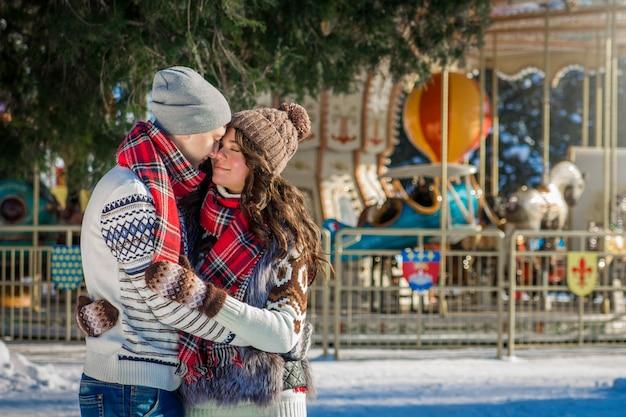 カルーセルで冬の公園でカップルを抱擁します。