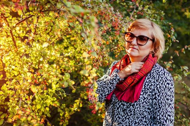 スタイリッシュな中年女性が秋の服やアクセサリーを着て秋の森でポーズ