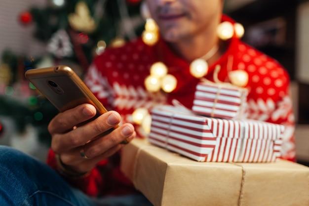 新年を買う男がスマートフォンを使用してプレゼント