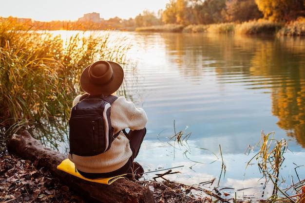 Турист с рюкзаком, сидя на берегу реки на закате