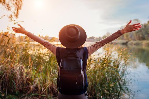 Путешественник с рюкзаком отдыхает у осенней реки на закате