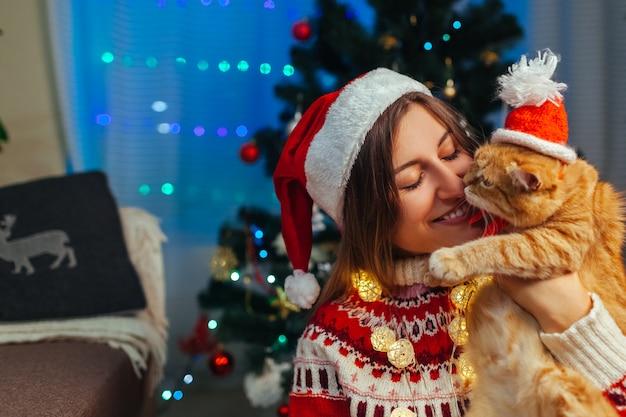 Празднование рождества с кошкой. женщина играя и целуя любимчика в шляпе санты новогодней елкой дома.