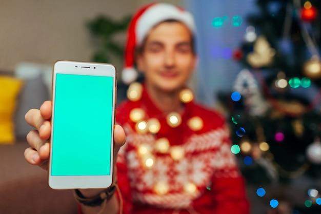 クリスマス用のスマートフォン。新年のプレゼントとして緑色の画面で携帯電話を保持している男。