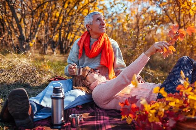 Счастливая пара старших, имея чай в осеннем лесу и наслаждаясь пикник