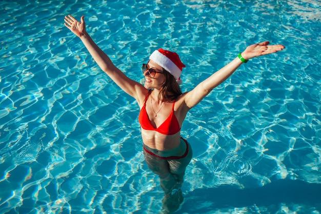 新年とクリスマス休暇。サンタさんの帽子とスイミングプールで腕を上げるビキニの女性。熱帯の休暇