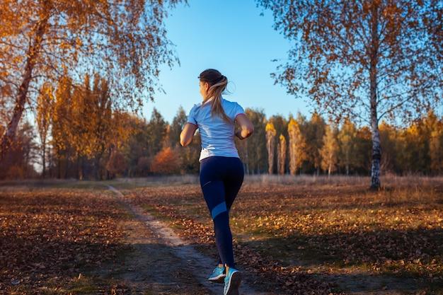 秋の公園でランナートレーニング。日没時の水のボトルで走っている女性。アクティブなライフスタイル