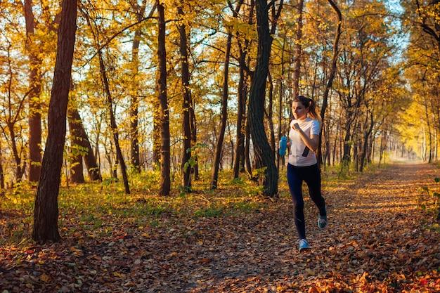 秋の公園で運動するランナー。日没時の水のボトルで走っている女性。アクティブなライフスタイル