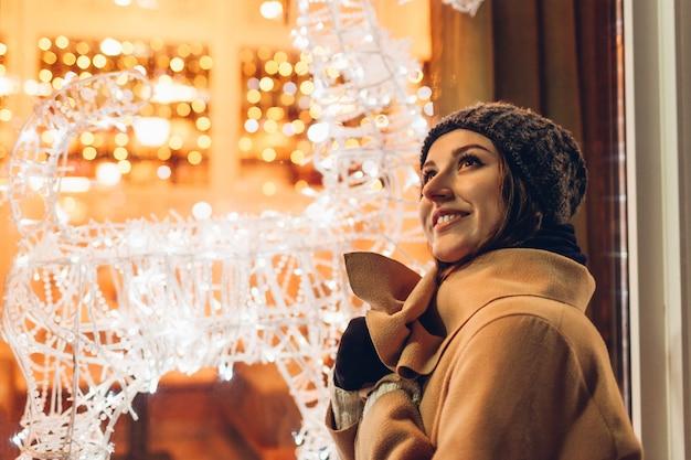 クリスマスと新年の楽しいコンセプト。夜に飾られた照らされたクリスマスショーケースで街を歩いている女性。